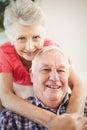 Senior woman embracing man at home