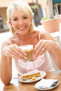 Senior Woman Enjoying Coffee And Cake Royalty Free Stock Image
