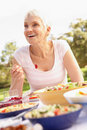 Senior Woman Enjoying Meal In Garden Stock Photography