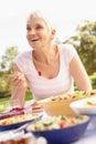 Senior Woman Enjoying Meal In Garden Stock Photography