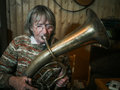 Senior woman is playing on a horn Royalty Free Stock Photo