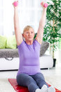 Senior woman exercise with weights at home sitting on a mat and Stock Photos