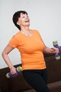 Senior woman exercising with barbells smiling happy fitness excercising at home Royalty Free Stock Image