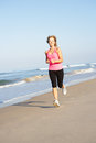 Senior Woman Exercising On Beach Stock Photography
