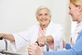 Senior woman with geriatric nurse happy women sitting on her bed Stock Photos