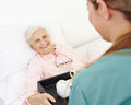 Senior woman getting breakfast happy women in bed in a nursing home Royalty Free Stock Photos