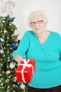Senior woman giving christmas present Royalty Free Stock Photography