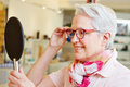 Senior woman with glasses looking happy new in mirror at optician Stock Images