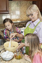 Senior woman with granddaughters mixing batter in kitchen women Royalty Free Stock Photo