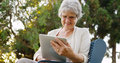 Senior woman happily surfing the web on tablet at park Royalty Free Stock Image