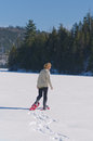 Senior woman having fun exercising snowshoes lake winter Stock Photo