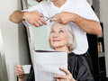 Senior woman having haircut at salon women with magazine and cup Royalty Free Stock Image