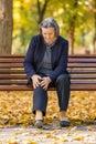 Senior woman having knee pain sitting on bench in park Royalty Free Stock Photo