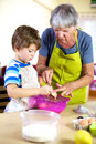 Senior woman helping grandson to cook and bake grandmother having a good time together at home playing Stock Images