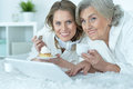 Senior woman with her adult daughter portrait of women eat tasty cake dring tea and watching something on laptop Royalty Free Stock Photography
