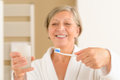 Senior woman hold toothbrush and glass water Royalty Free Stock Photo