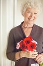 Senior woman holding a bouquet of fresh flowers happy Royalty Free Stock Images