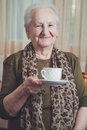 Senior woman holding coffee mug and smiling Royalty Free Stock Photo