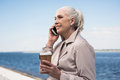 Senior woman holding disposable coffee cup and talking on smartphone