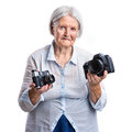Senior woman holding old analogue and modern digital cameras in hands choice concept Royalty Free Stock Images