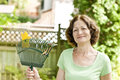 Senior woman holding rake smiling for yard work outside Stock Images