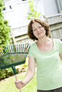 Senior woman holding rake smiling for yard work outside Royalty Free Stock Images