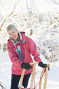 Senior Woman Holding Sledge In Snowy Landscape Royalty Free Stock Photography