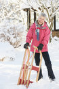 Senior Woman Holding Sledge In Snowy Landscape Stock Photo