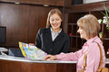 Senior woman in hotel looking at city map women with female receptionist Stock Photo