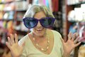 Senior woman in huge sunglasses at shopping mall Royalty Free Stock Photos