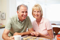 Senior Woman With Husband Baking Cookies In Kitchen Royalty Free Stock Photo