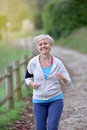 Senior woman jogging outdoors listening to music Royalty Free Stock Photo