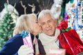 Senior woman kissing man with christmas presents loving women men at store Royalty Free Stock Image