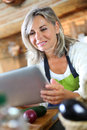 Senior woman in kitchen looking at tablet for recipe cooking with help of on Royalty Free Stock Photos