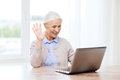 Senior woman with laptop having video chat at home Royalty Free Stock Photo