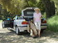 Senior woman leaning on car boot beside golf bag smiling portrait Royalty Free Stock Photo