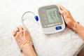 Senior woman with low blood pressure closeup of a s hands checking her on a home meter results are Stock Image