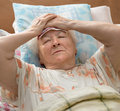 Senior woman lying at bed sick Royalty Free Stock Photo
