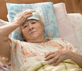 Senior woman lying at bed sick Royalty Free Stock Photos