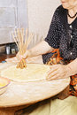 Senior woman making holes in bread Stock Photography