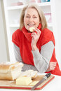 Senior Woman Making Sandwich In Kitchen Stock Photo