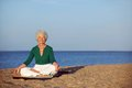 Senior woman meditating on beautiful beach portrait of the the seashore with lots of copyspace elder doing relaxation exercise Royalty Free Stock Images