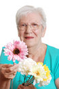 Senior woman offering a fake daisy focus on flower Stock Images
