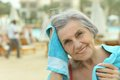 Senior woman at pool with towel smiling Royalty Free Stock Image