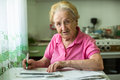 Senior woman populates handle her utility bills notices sitting at the table in the kitchen Stock Photos