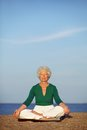 Senior woman practicing morning yoga with ocean in background old caucasian doing relaxation exercise on beach meditation Royalty Free Stock Photography
