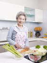 Senior woman preparing meal in kitchen asian cutting carrot to make salad Royalty Free Stock Photos