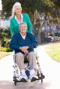 Senior Woman Pushing Husband In Wheelchair Stock Photos