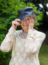 Senior woman putting on her hat smoothing down hair under the brim while keeping an eye the camera Stock Photo