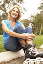 Senior Woman Putting On In Line Skates In Park Stock Photos